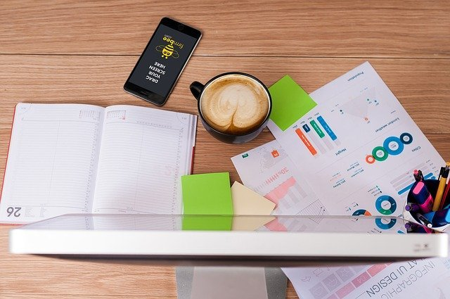 Several items on a faux wooden desktop including a cup of cappuchino, a phone, some bills, Post-It notes and a cup of colorful pens
