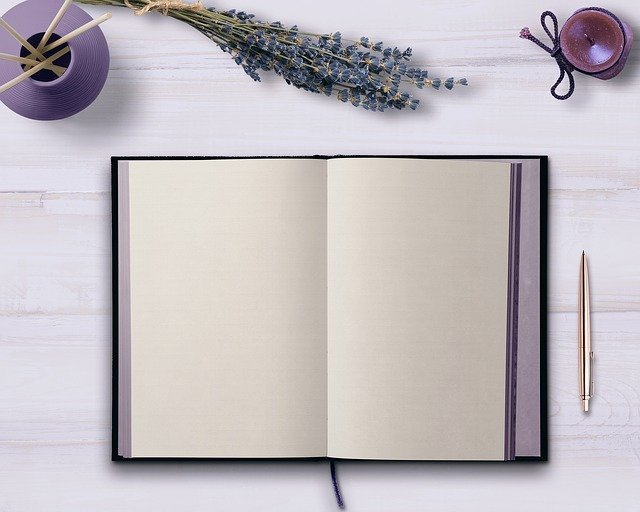 Learning how to become a freelance writer with an empty notebook on purple table