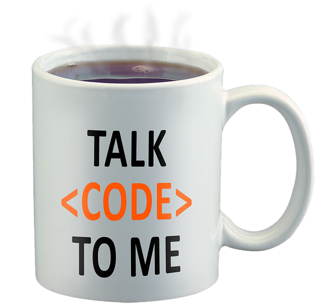 White coffee cup filled with black coffee with talk code to me printed on it.