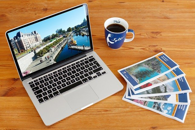 Planning to freelance online while traveling with a laptop, cup of coffee and a few travel brochures on a table