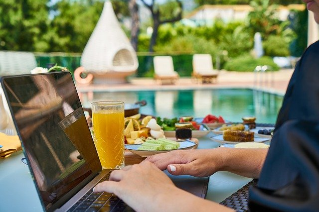 Woman on laptop working on multiple streams poolside with glass of orange juice and fruit on a plate