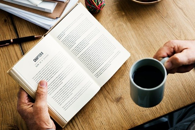 Male freelance writer reading a book for writing inspiration - one of the best writing tips