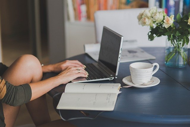 Young woman at table working on multiple income streams at her laptop with an empty cup of coffee